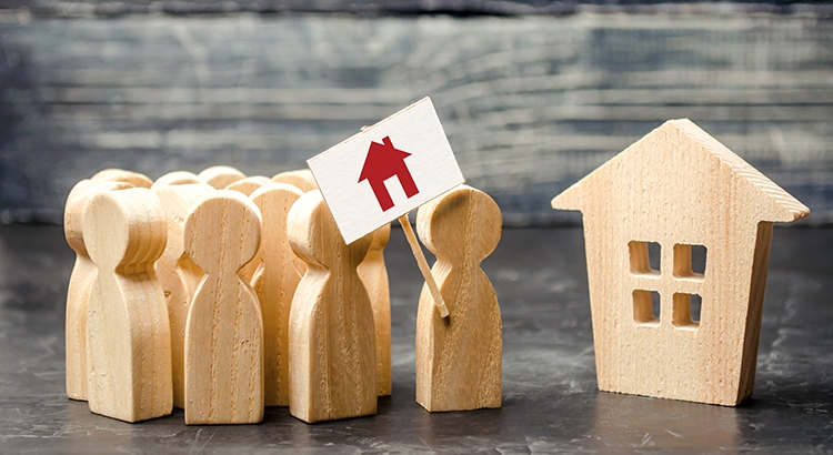 wooden people with a house flag bidding on a wooden house