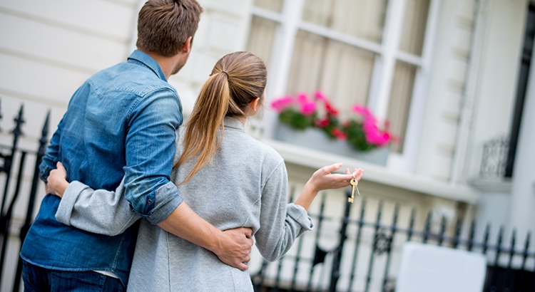 couple holding eachother and a house key